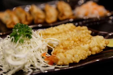 shrimp in tempura on the white plate and metal chopsticks