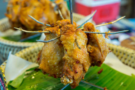 Thai Fried Chicken impaled with sharp metal on banana leaf Stock Photo