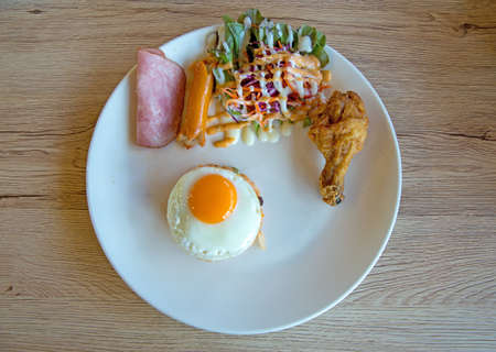 Prepare sausage, ham, fried egg and fried Chicken for breakfast, serve in the white plate Stock Photo
