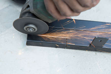 Close-up of worker cutting steel with grinder, focus selective. 版權商用圖片
