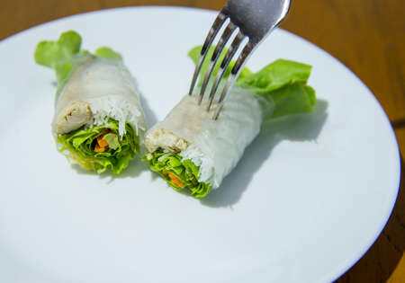 Noodle salad with mackerel wrapped in rice paper and fork on white plate. Zdjęcie Seryjne