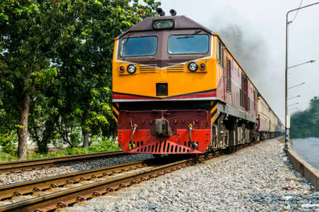 Thailand Train running on metal railway parallel with the tree. Banco de Imagens