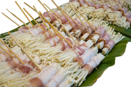 Raw bacon wrapped mushroom for barbecued with Skewer die cut on white background.