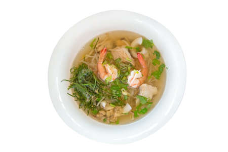 Top view of Seafood noodles in white bowl.