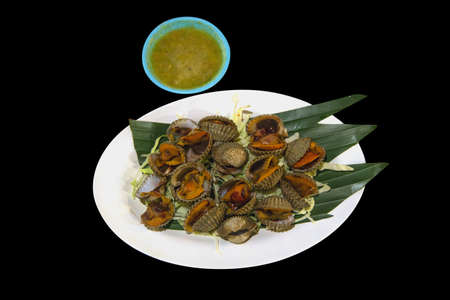 Big Steamed cockle Boiled cockles with tasty sauce in black isolated.