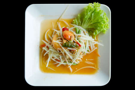 Top view of Thai style spicy papaya Salad (Som tum) focus selective, with black background