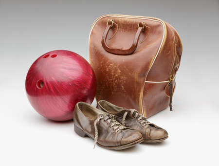 Vintage Red Bowling Ball, Weathered Leather Bag and Brown Shoes Isolated on White photo