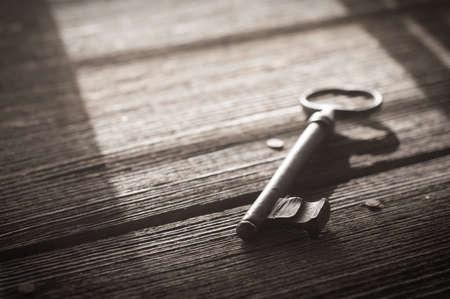Rusty Old Skeleton Key on Dark Rustic Barnwood With Window Light