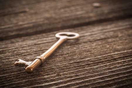 Old Brass Skeleton Key on Dark Rustic Barnwood Stock Photo
