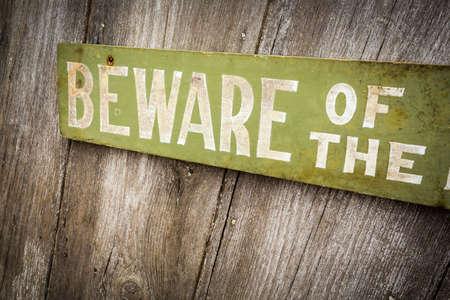 古いすり切れた木製の柵に犬のサインに注意します。