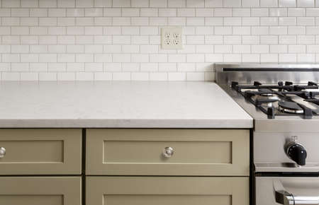 countertop: Kitchen Counter with Subway Tile, Stainless Steel oven stove, Shaker Cabinets