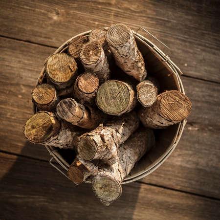 カットの薪の素朴な木製の床の古いバスケット