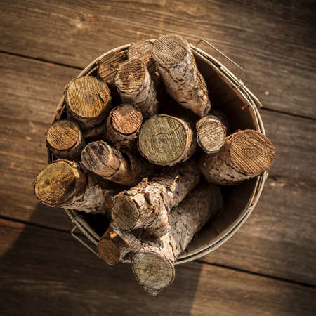 Old Basket of Cut Firewood on Rustic Wood Floor