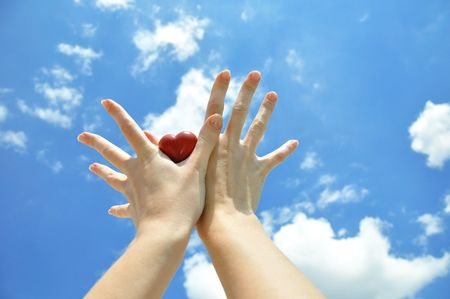Heart in female hands against the sky photo