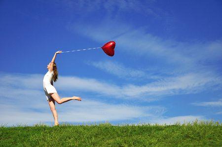 Mädchen mit eine rote Kugel in Form des Herzens auf den Hintergrund des Himmels  Standard-Bild - 5295926