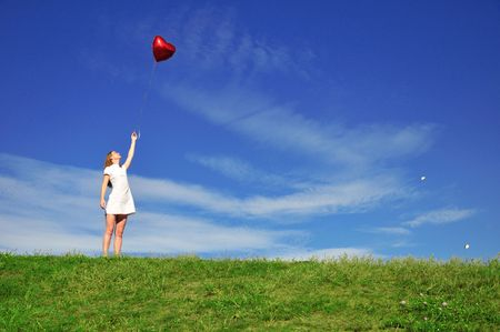 girl with a red ball in the form of heart on the background of the sky