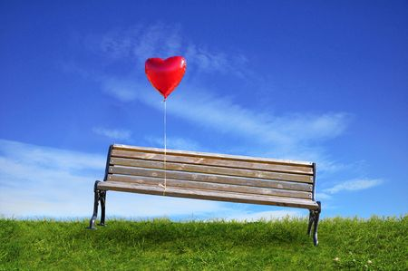 red balloon in a heart attached to the bench