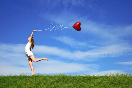 girl with a red ball in the form of heart on the background of the sky photo