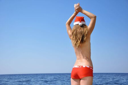 Woman wears a hat of Santa Claus on the beach photo