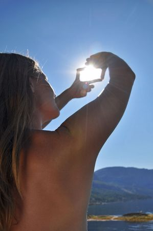 girl makes a frame for the sun out of the hands Stock Photo - 5522084