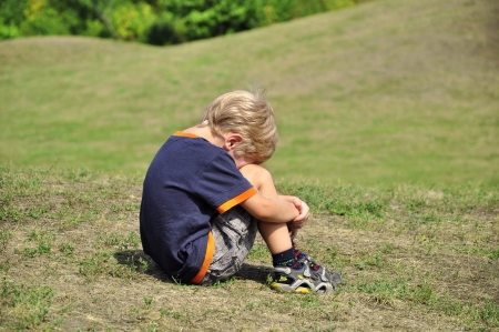 Young blond boy desperation body language Stock Photo