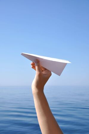 throwing a paper plane against the blue sky
