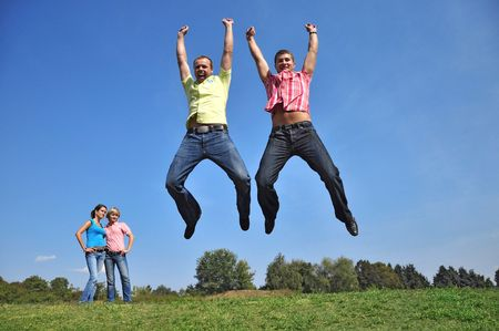 Two guys are jumping with their hands up, two girls watched