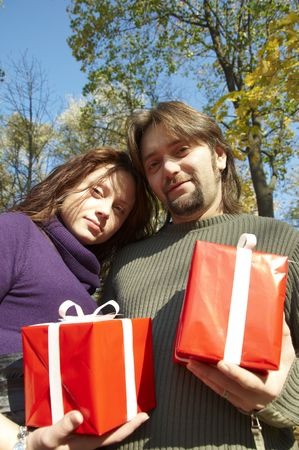 young couple gives gifts, in the autumn park photo