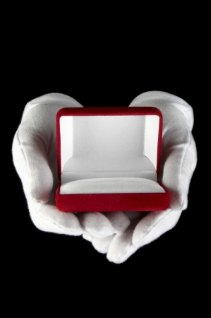 hands in white gloves presented with an open box for jewelry photo
