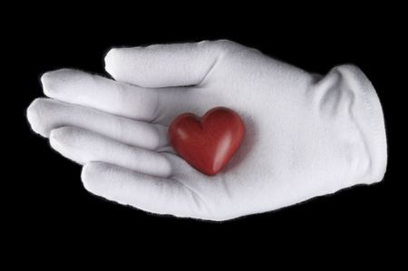 brick red heart in his hand in a white glove Stock Photo