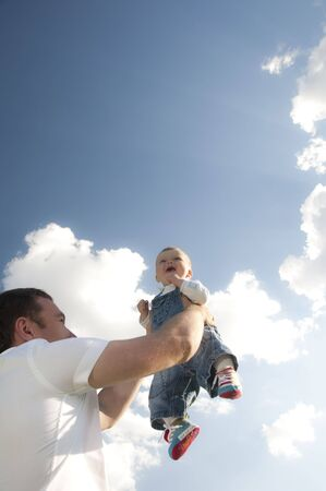 vaderlijk: Father throws baby son in her arms on a background of blue sky, paternal care Stockfoto