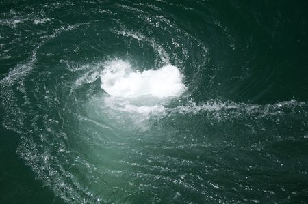 A green water vortex that funnels below the surface.
