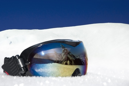 protective eyewear for winter sports and recreation on the background of snowy mountains and blue sky Standard-Bild