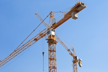 towering: Crane towering overhead against blue sky Stock Photo