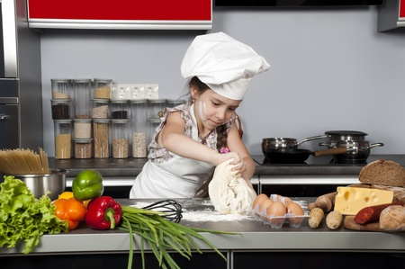 little girl chef knead the dough on the kitchen table with raw food photo
