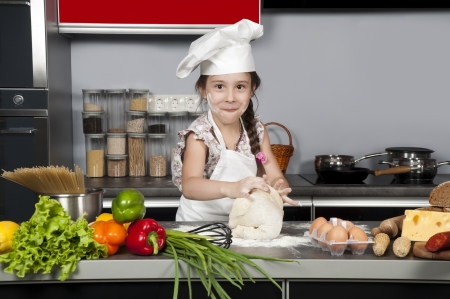 little girl chef knead the dough on the kitchen table with raw food 免版税图像