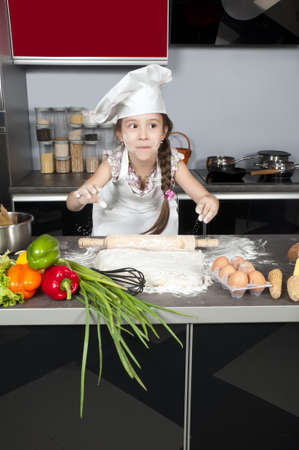 little girl chef kneads the dough with a rolling pin on the kitchen table with raw food photo
