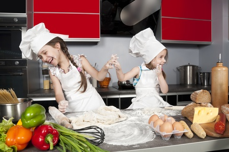 two little girls having fun on the kitchen table with raw food, clothing cooks Stock Photo - 9708006
