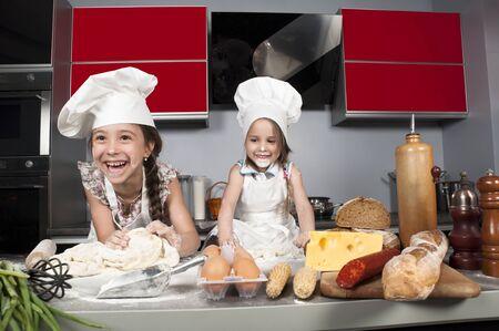 chicas divirtiendose: dos ni�as que se divierten en la mesa de la cocina con alimentos crudos, ropa de cocina