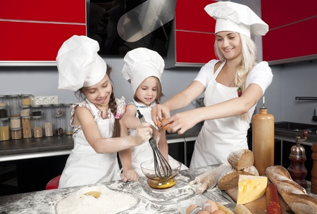 Mom teaches two daughters to cook at the kitchen table with raw food, clothing cooks