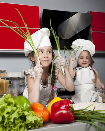 two little girls in clothes cooks in the kitchen at the table with raw food, with bunches of green onions in the hands of Stock Photo