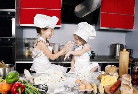 frutas divertidas: dos ni�as que se divierten en la mesa de la cocina con alimentos crudos, ropa de cocina