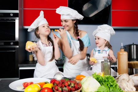 Mom teaches two daughters to cook at the kitchen table with raw food, clothing cooks photo