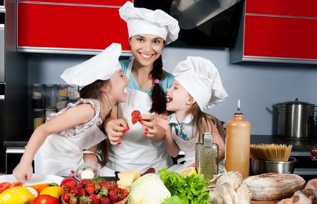 Mama lehrt zwei Töchter, um sich an den Küchentisch mit rohen Lebensmitteln, Kleidung Köche kochen Standard-Bild - 9808717