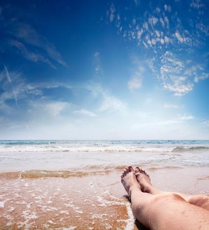 pieds féminins dans l'eau de mer cristalline
