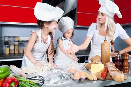 ni�os cocinando: Mam� ense�a dos hijas para cocinar en la mesa de la cocina con alimentos crudos, ropa de cocina Foto de archivo