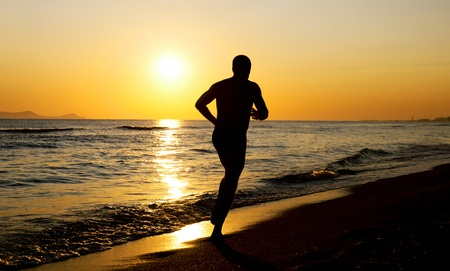 Silhouette of a running man on the beach