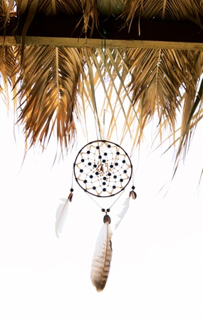 Dreamcatcher moved by wind under a roof on a white background