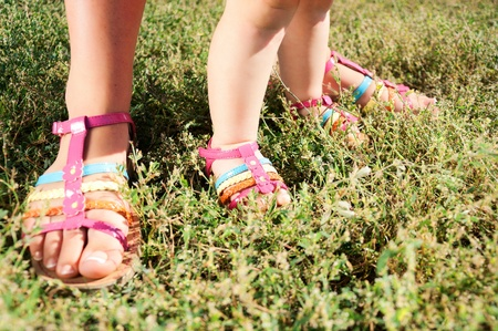 Two pairs of feet in green grass. Walking in grass, mothers and kids feet in sandals