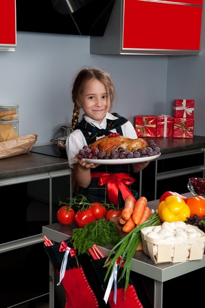 On Christmas Eve, the little girl in the kitchen by a uniformed chef serves roasted turkey on a platter with grapes. Kitchen table with fresh produce photo